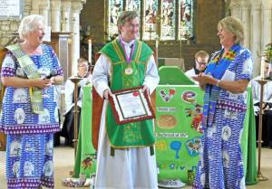 Mary & Chuff ambushed Fr Gary with a special award from Bishop Matthias